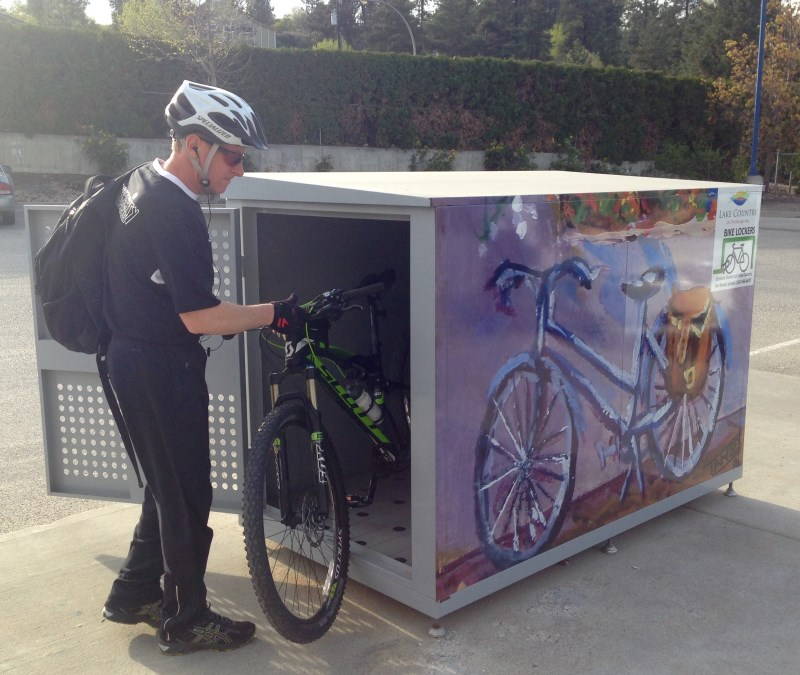 man wearing bike helmet removing bike from locker at municipal hall
