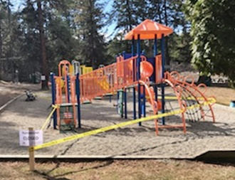 playgrounds are surrounded by yellow caution tape with playground closed sign